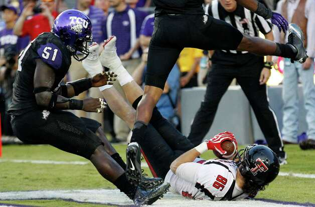 Texas Tech wide receiver Alex Torres (86) lands in the end zone holding the game-winning touchdown pass in triple overtime as TCU linebacker Kenny Cain (51) looks on ending the NCAA college football game, Saturday, Oct. 20, 2012, in Fort Worth, Texas. Texas Tech won 56-53. (AP Photo/LM Otero) Photo: LM Otero, Associated Press / AP