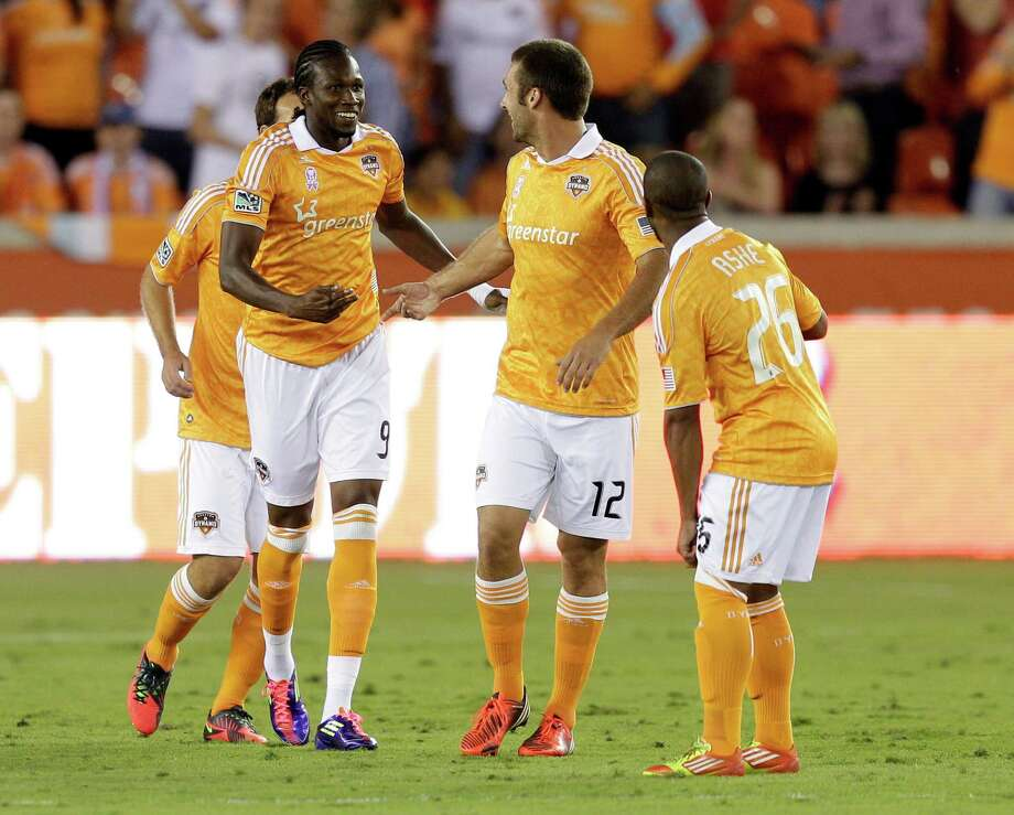 HOUSTON,TX - OCTOBER 20:  Macoumba Kandji #9 is congratulated by Will Bruin #12 and Corey Ashe #26 of the Houston Dynamo after scoring in the first half against the Philadelphia Union at BBVA Compass Stadium on October 20, 2012 in Houston, Texas. Photo: Bob Levey, Getty Images / 2012 Getty Images