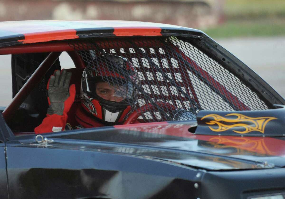 A driver waves during a yellow-flag lap of the late-model modifieds race at the San Antonio Speedway on Texas Highway 16 South on Saturday, Oct. 20, 2012.
