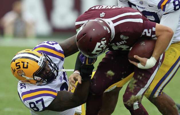 LSU defensive end Chancey Aghayere pulls Texas A&M quarterback Johnny Manziel's face mask during the fourth quarter of a NCAA football game, Saturday, Oct. 20, 2012, in College Station. LSU won 24-19. Photo: Nick De La Torre, Houston Chronicle / © 2012  Houston Chronicle