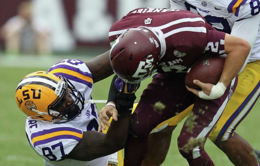 LSU defensive end Chancey Aghayere pulls Texas A&M quarterback Johnny Manziel's face mask during the
