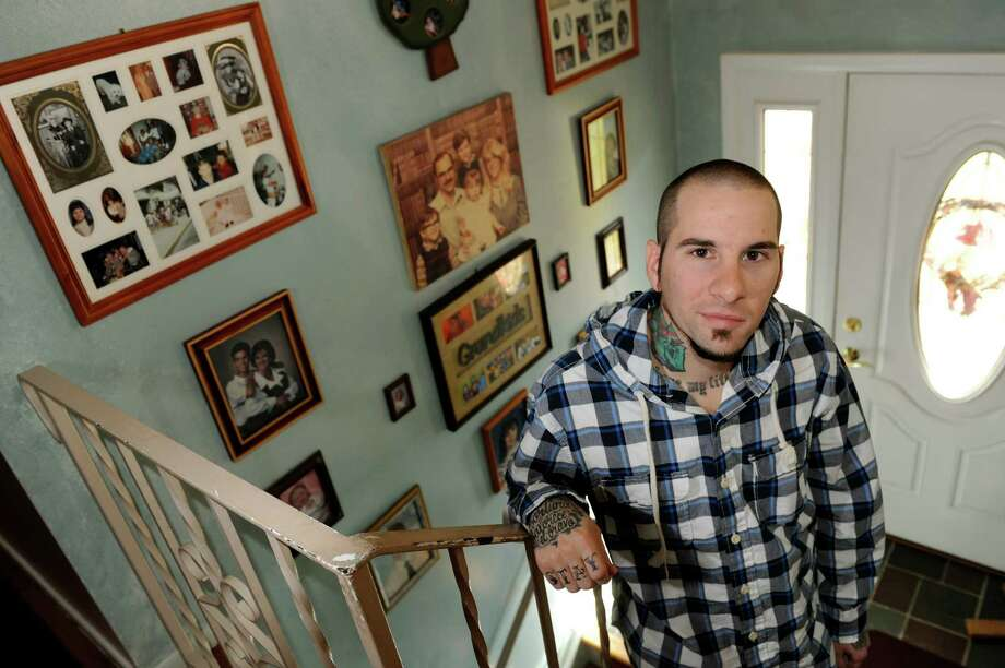 "Tim Satalino with family photographs on Wednesday, Oct. 17, 2012, at his parent's home in Colonie, N.Y. Satalino went to Catholic school but now is considered a ""none."" (Cindy Schultz / Times Union) Photo: Cindy Schultz / 00019710A"
