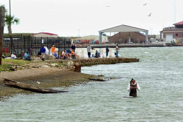 People fish in the water an on the shore at Seawolf Park on Pelican Island Thursday, Oct. 18, 2012, in Galveston. Photo: Brett Coomer, Houston Chronicle / © 2012 Houston Chronicle