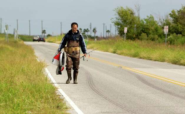 Joe Zeng, of Missouri City, walks along Seawolf Parkway after fishing on Pelican Island Thursday, Oct. 18, 2012, in Galveston. Photo: Brett Coomer, Houston Chronicle / © 2012 Houston Chronicle