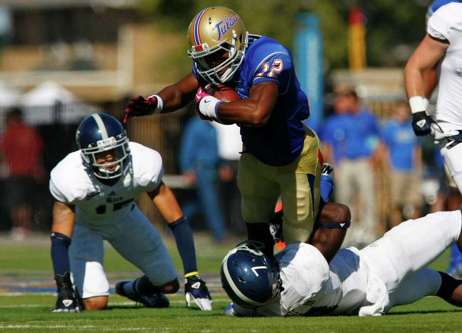 Tulsa's Jordan James is stopped by Rice's Julius White during the first half of an NCAA college football game Saturday, Oct 20, 2012, in Tulsa, Okla. (AP Photo/Tulsa World, Tom Gilbert) Photo: Tom Gilbert, Associated Press / Tulsa World