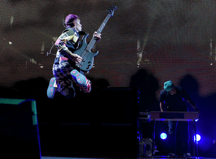 """Michael """"Flea"""" Balzary of the Red Hot Chili Peppers jumps around on stage while performing at Toyota Center on Saturday, Oct. 20, 2012, in Houston. Photo: Joe Buvid, For The Chronicle / © 2012 Joe Buvid"""