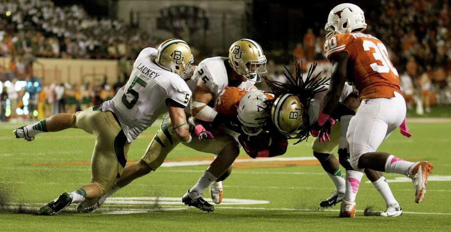 Texas's D.J. Monroe is tackled by Baylor defenders, left to right, Eddie Lackey, Lache Seastrunk and K.J. Morton in the second quarter. Photo: Jay Janner, McClatchy-Tribune News Service / Austin American-Statesman