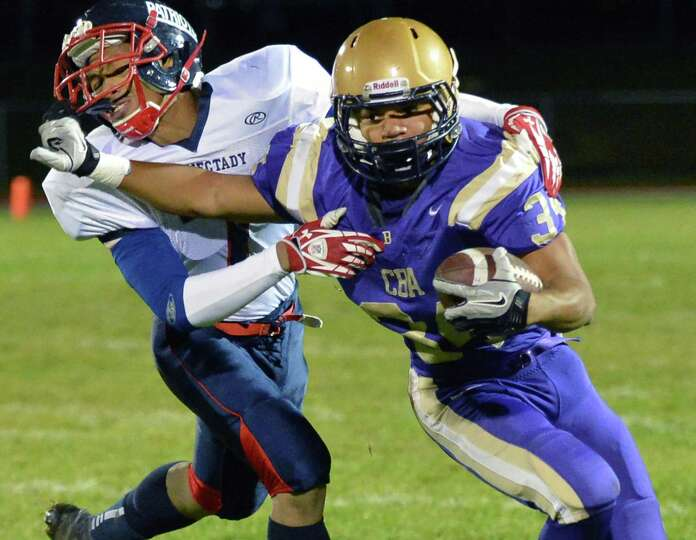 CBA's #34 Cameron Wynn gets away from Schenectady defender Rainey Hassan, left, during the Section I