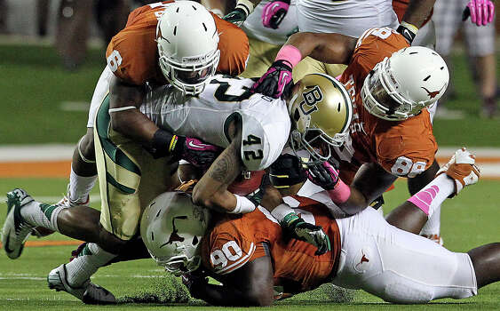Longhorn defenders Quandre Diggs (6), Cedric Reed (88) and Malcolm Brown (90) combine to stop Levi Norwood in the second half as Texas defeats  Baylor 56-50 at Darrell K Royal - Texas Memorial Stadium Stadium  on October 20, 2012. Photo: Tom Reel, Express-News / ©2012 San Antono Express-News