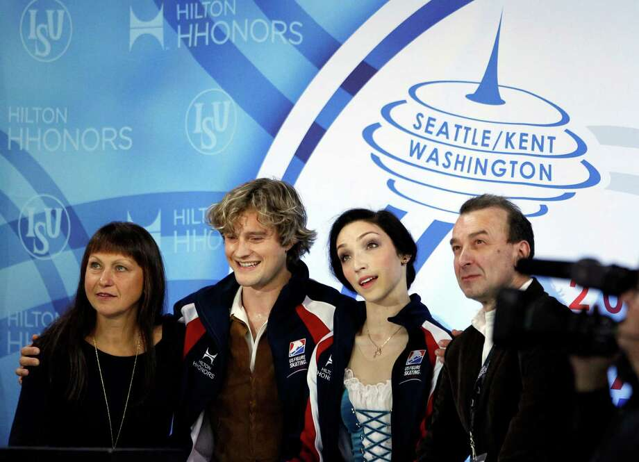 Meryl Davis, second from right, and partner Charlie White, second from left, watch for their scores with coaches Marina Zueva, left, and Oleg Epstein following the ice dance short dance. Photo: AP
