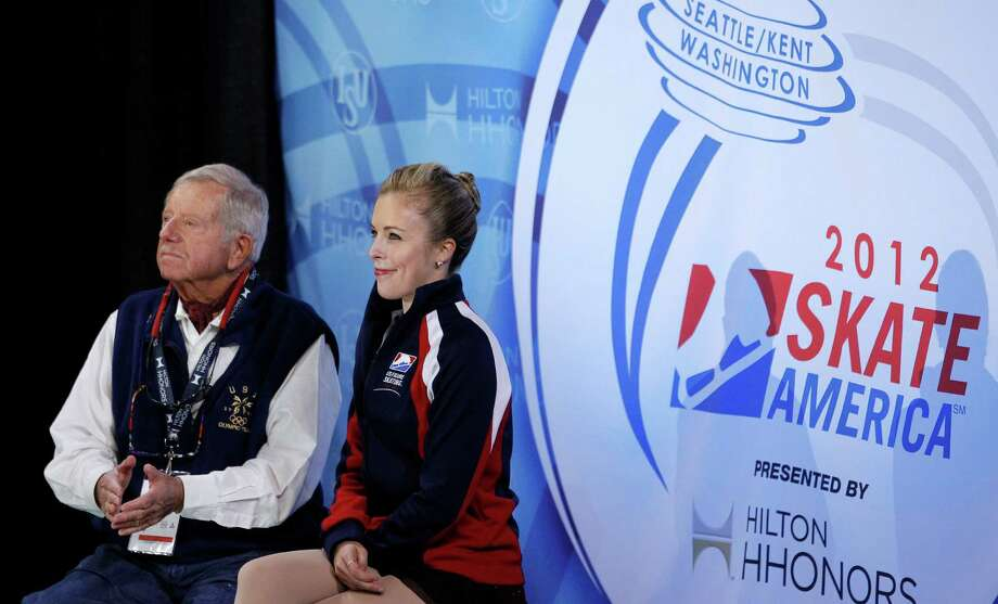 Ashley Wagner, right, sits with her coach, John Nicks, as she watches for her score following her skate in the ladies short program. Photo: AP