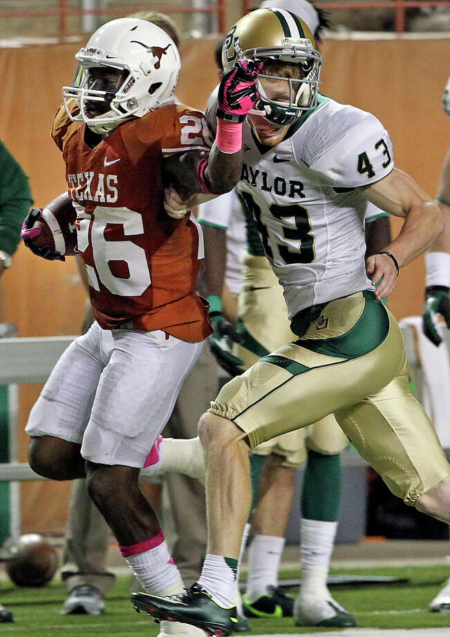 D.J. Monroe shakes off place kicker Aaron Jones with a stiff arm to the facemask on a long return in the second half as Texas hosts Baylor at Darrell K Royal - Texas Memorial Stadium Stadium  on October 20, 2012. Photo: Tom Reel, Express-News / ©2012 San Antono Express-News