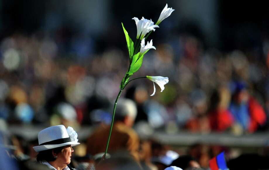 "A woman holds a white flower during a special mass to name seven new saints in St Peter's square at Vatican on October 21, 2012. Pope Benedict XVI named today seven new saints, Kateri Tekakwitha of the US, Jacques Berthieu of France, Maria Anna Cope of Germany, Pedro Calungsod from the Philippines, Maria Schaffer of Germany, Giovanni Battista Piamarta of Italy, Maria del Carmen of Spain, marking the start of a ""Year of Faith"" aimed at countering the rising tide of secularism in the West. AFP PHOTO / TIZIANA FABITIZIANA FABI/AFP/Getty Images Photo: TIZIANA FABI, AFP/Getty Images / AFP"