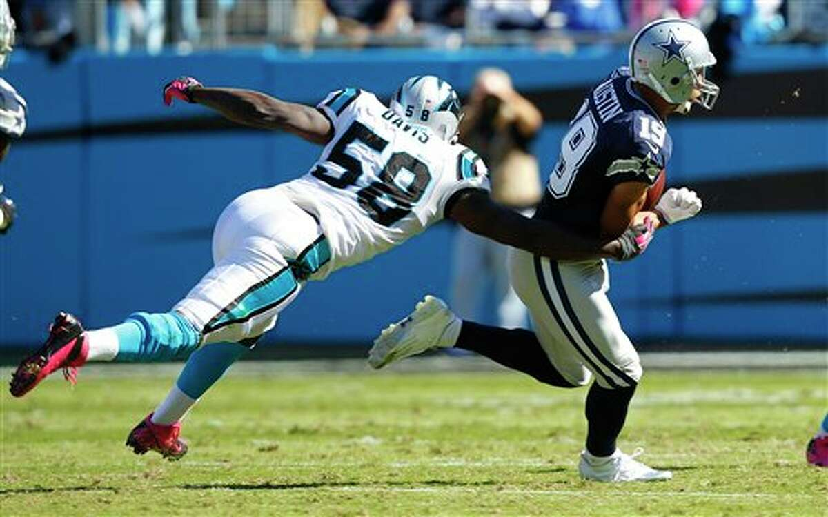 Dallas Cowboys wide receiver Miles Austin (19) has the ball stripped by Carolina Panthers outside linebacker Thomas Davis (58) during the first half of an NFL football game, Sunday, Oct. 21, 2012, in Charlotte. (AP Photo/Chuck Burton)
