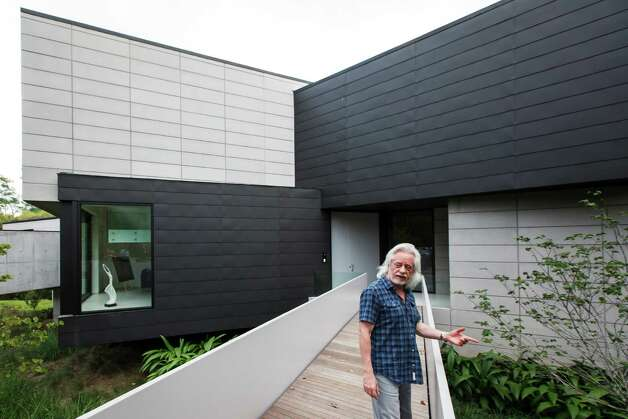 Michael Bleyzer stands outside the front entrance to his 15,000-square-foot house overlooking a wooded nature preserve on the banks of Buffalo Bayou and designed by the firm Stern & Bucek, Wednesday, Oct. 10, 2012, in Houston.  The Bleyzer House is on this year's American Institute of Architects Home Tour 2012. Photo: Michael Paulsen, Houston Chronicle / © 2012 Houston Chronicle