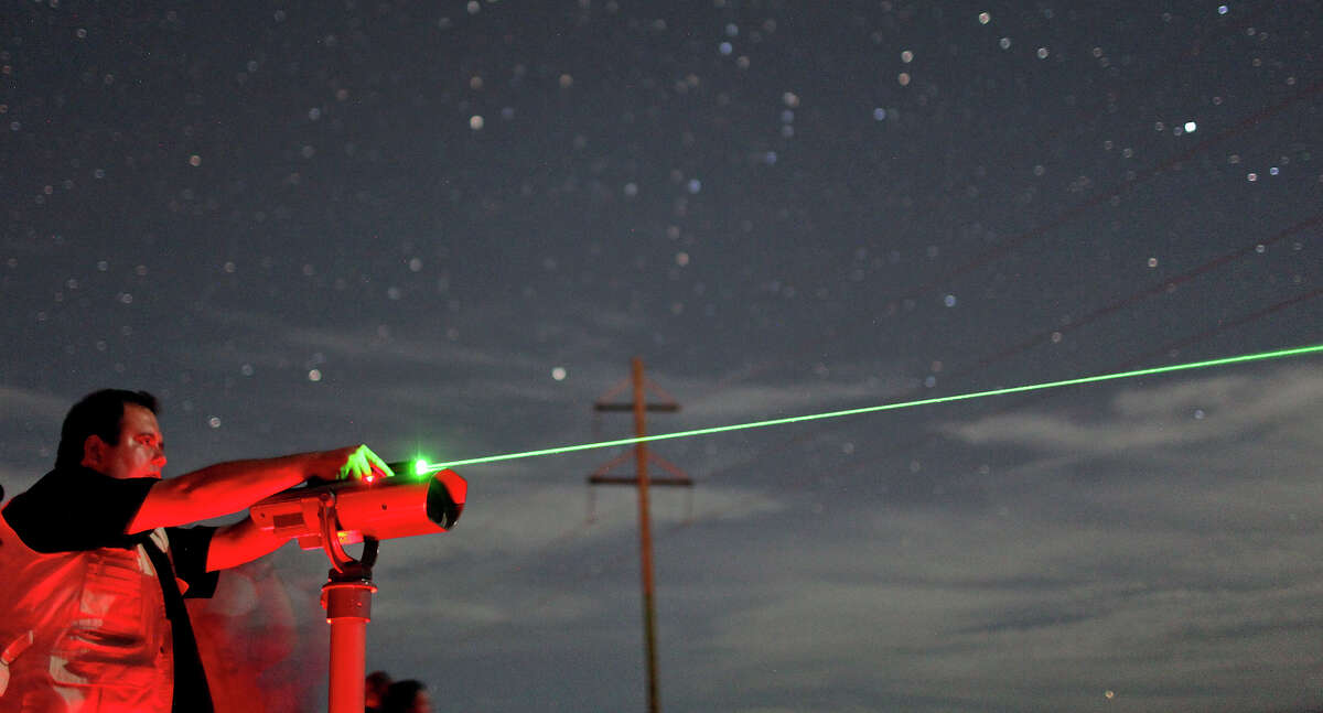 Laredo Paranormal Research Society director and co-founder Ismael Cuellar points a laser at the Marfa Lights on Saturday Oct. 20, 2012 at the Marfa Lights Viewing Area, nine miles east of Marfa, Tx. The LPRS was part of the Border Zone International UFO Festival held in Presidio, Tx.