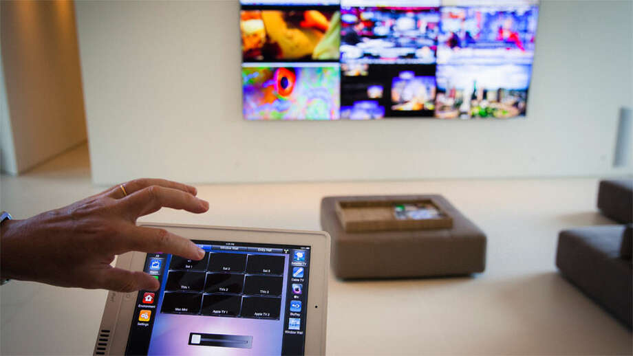 Michael Bleyzer uses an  iPad control system that operates a series of nine televisions and other  electronic components in his 15,000-square-foot house overlooking a wooded  nature preserve on the banks of Buffalo Bayou and designed by the firm Stern  & Bucek, Wednesday, Oct. 10, 2012, in Houston. The Bleyzer House is on this year's American Institute  of Architects Home Tour 2012. ( Michael Paulsen / Houston Chronicle )