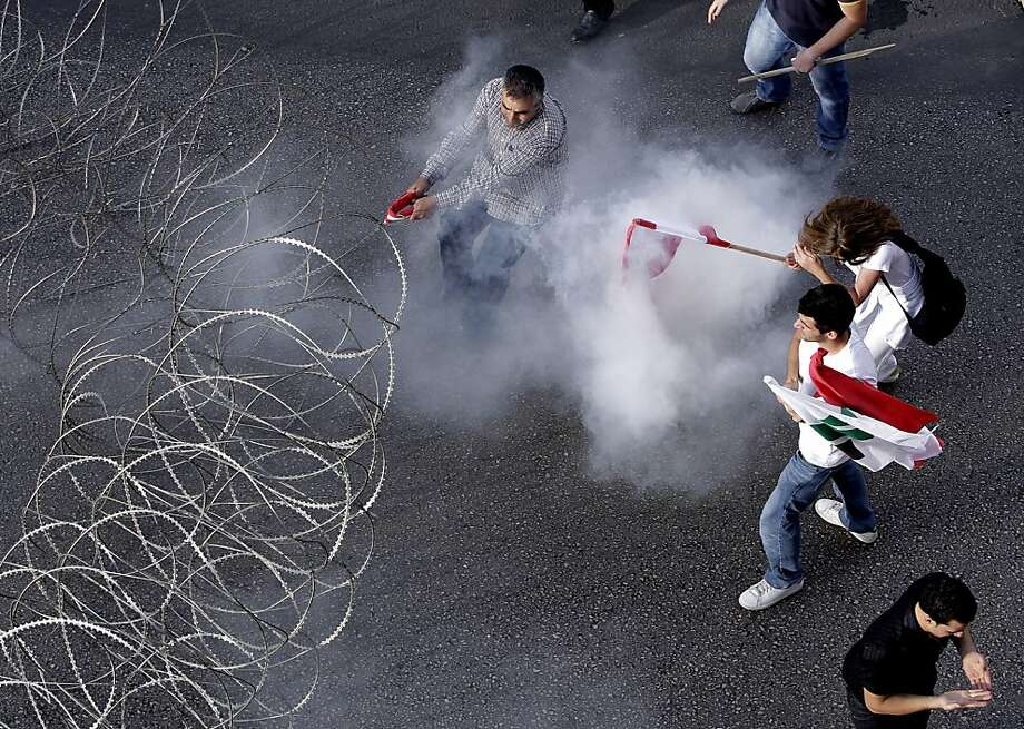 Lebanese protesters are tear-gassed as they pull a barbed-wire barrier during clashes after the funeral for the intelligence chief who was assassinated. Photo: Hussein Malla, Associated Press