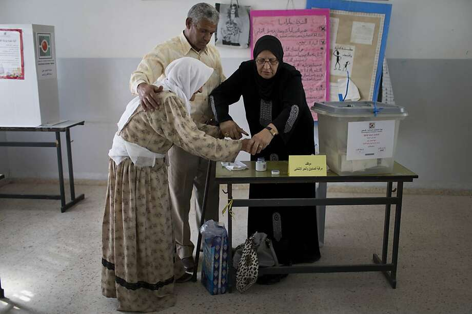 A Palestinian elderly woman is helped to cast her vote at a polling station in West Bank, where Palestinians largely elected the dominant Fatah party. Photo: Bernat Armangue, Associated Press