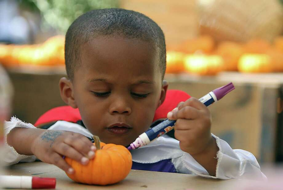 Three-year-old Juvon Pollard decorates a small pumpkin during the Zoo Boo weekend at the Houston Zoo Sunday, Oct. 21, 2012, in Houston. The Zoo Boo event includes halloween themed contest and activities for kids. Photo: James Nielsen, Chronicle / © Houston Chronicle 2012