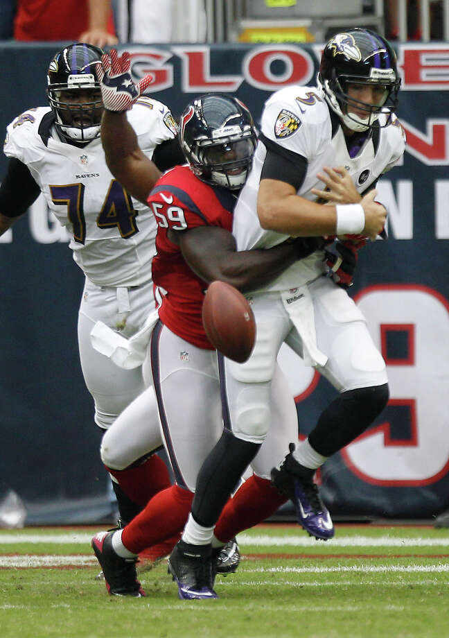 Baltimore Ravens quarterback Joe Flacco (5) gets the ball stripped from him by Houston Texans linebacker Whitney Mercilus (59) during the first quarter at Reliant Stadium on Sunday, Oct. 21, 2012, in Houston. Photo: Brett Coomer, Houston Chronicle / © 2012  Houston Chronicle