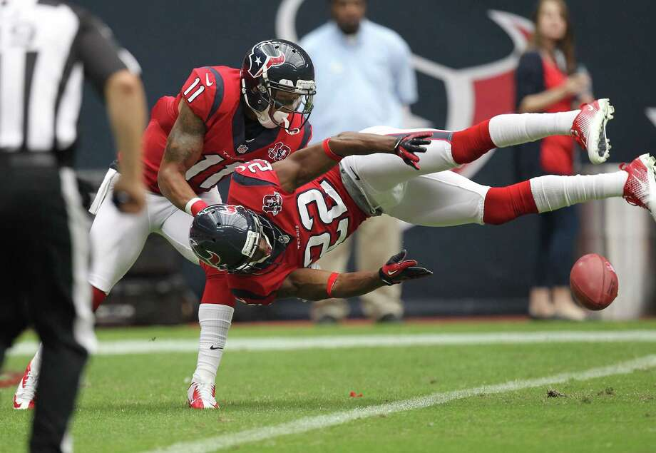 Houston Texans defensive back Alan Ball (22) and Houston Texans wide receiver DeVier Posey (11) try to keep the ball just inside of the line during the first quarter of an NFL football game, Sunday, Oct. 21, 2012, at Reliant Stadium in Houston. Photo: Nick De La Torre, Houston Chronicle / © 2012  Houston Chronicle