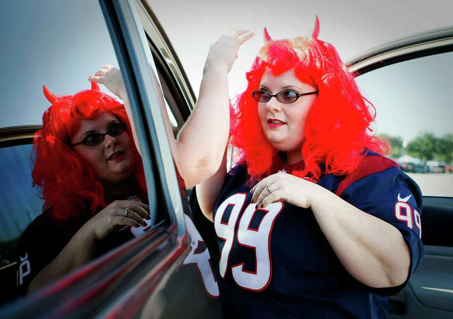 Tracey Brackin, of Houston, gets her wig adjusted by her friend Danielle Tindle, of Cypress, before the Houston Texans game against the Baltimore Ravens, Sunday, Oct. 21, 2012, in Reliant Stadium in Houston. Photo: Nick De La Torre, Houston Chronicle / © 2012  Houston Chronicle