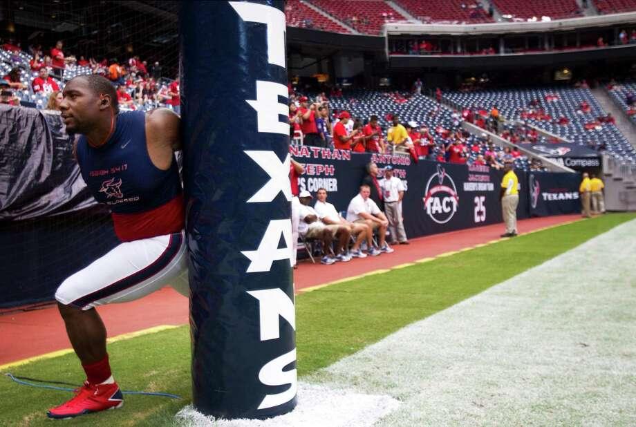 Houston Texans defensive end Antonio Smith stretches before the Texans game against the Baltimore Ravens at Reliant Stadium on Sunday, Oct. 21, 2012, in Houston. Photo: Brett Coomer, Houston Chronicle / © 2012  Houston Chronicle