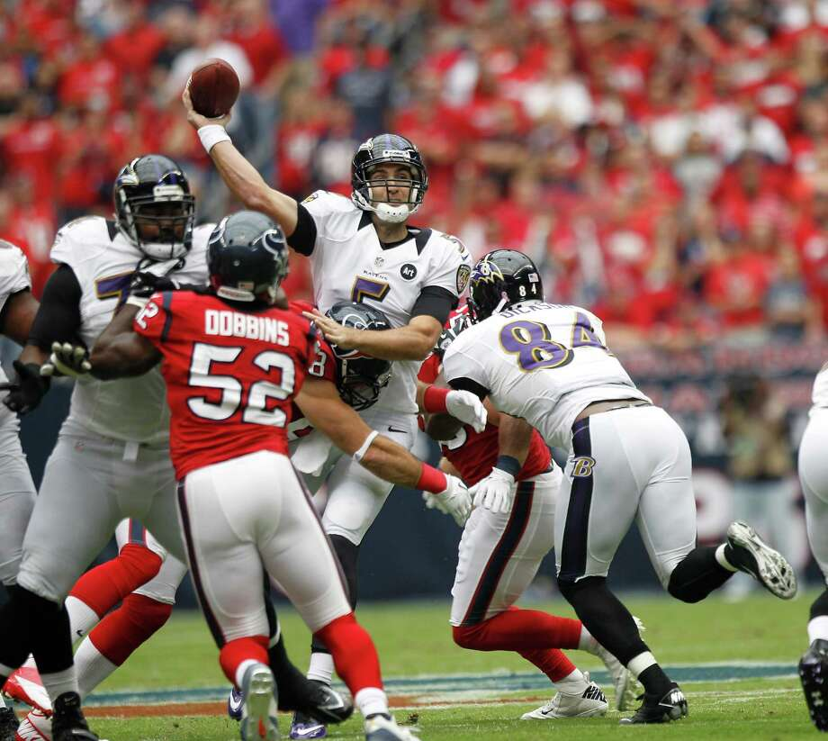 Baltimore Ravens quarterback Joe Flacco (5) throws the ball as he is tackled by Houston Texans defensive end J.J. Watt (99) during the first quarter at Reliant Stadium on Sunday, Oct. 21, 2012, in Houston. Photo: Brett Coomer, Houston Chronicle / © 2012  Houston Chronicle