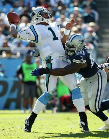 Carolina Panthers quarterback Cam Newton (1) tries to get off a pass as Dallas Cowboys nose tackle Jay Ratliff (90) tackles him during the second half of an NFL football game, Sunday, Oct. 21, 2012, in Charlotte, N.C. (AP Photo/Bob Leverone) Photo: Bob Leverone, Associated Press / FR170480 AP