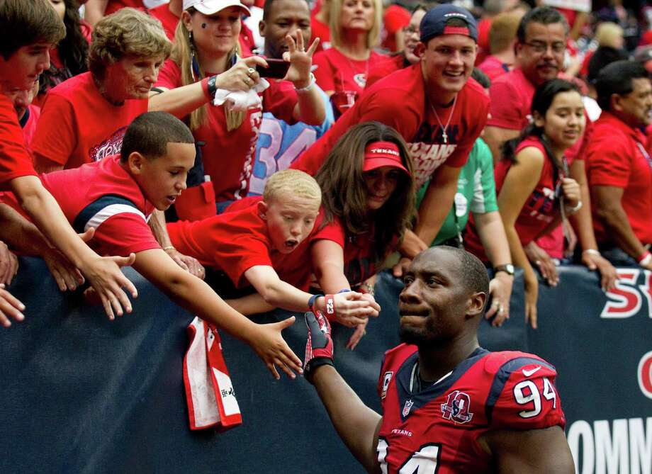 Houston Texans defensive end Antonio Smith (94) high fives with the fans after the Texans beat the Baltimore Ravens at Reliant Stadium on Sunday, Oct. 21, 2012, in Houston. The Texans beat the Ravens 43-13. Photo: Brett Coomer, Houston Chronicle / © 2012  Houston Chronicle