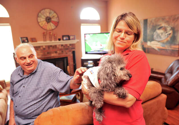 Valerie Lacayo of Pawsitive Memories provides hospice care for Harry, the terminally ill and blind dog of Ronnie Esper (left) in Esper's home recently. Photo: For The Express-News