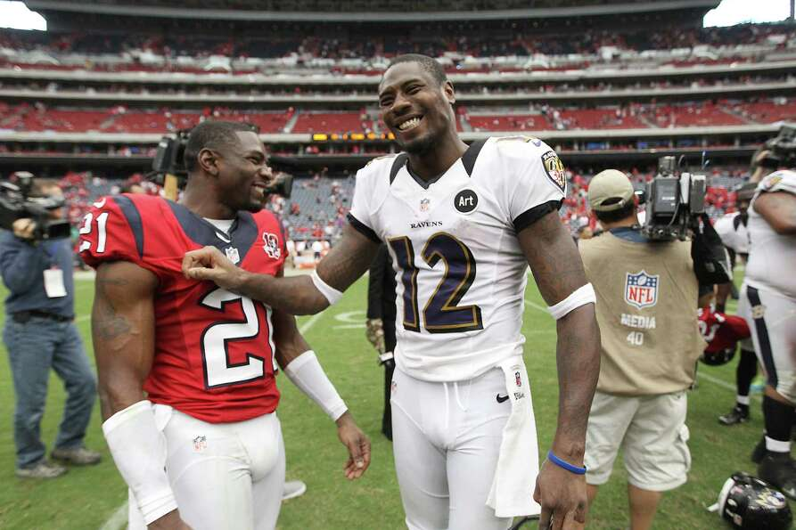 Baltimore Ravens wide receiver Jacoby Jones (12) chats with former Texan teammate Brice McCain (21)