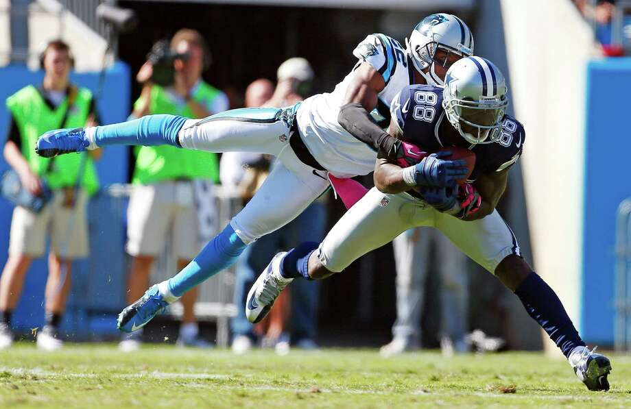 Carolina Panthers defensive back Josh Thomas (22) tackles Dallas Cowboys wide receiver Dez Bryant (88) during the second half of an NFL football game on Sunday, Oct. 21, 2012, in Charlotte, N.C. (AP Photo/Bob Leverone) Photo: Bob Leverone, Associated Press / FR170480 AP