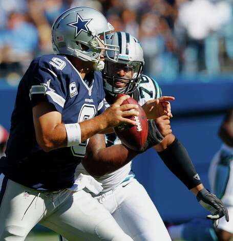 Dallas Cowboys quarterback Tony Romo (9) looks for an open receiver as Carolina Panthers defensive end Greg Hardy (76) defends during the second half of an NFL football game, Sunday, Oct. 21, 2012, in Charlotte, N.C. (AP Photo/Chuck Burton) Photo: Chuck Burton, Associated Press / AP