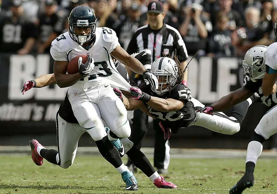 Jacksonville Jaguars running back Rashad Jennings (23) runs as Oakland Raiders linebacker Philip Wheeler (52) reaches for him during the second quarter of an NFL football game, Sunday, Oct. 21, 2012, in Oakland, Calif. (AP Photo/Marcio Jose Sanchez) Photo: Marcio Jose Sanchez, Associated Press