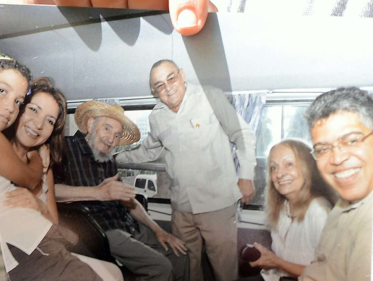 An image of former Cuban President Fidel Castro (3-L) is held up by former Venezuelan Vice-President Elias Jaua in La Havana on October 21, 2012. The photograph shows the former Cuban leader alongside Jaua (R), as well as Cuban National Hotel director, Antonio Martinez (C), Castro´s wife, Dalia Soto del Valle (2-R), and an unidentified woman and child. According to Jaua, Castro conversed with him for many hours and is in very good health. AFP PHOTO/ADALBERTO ROQUEADALBERTO ROQUE/AFP/Getty Images