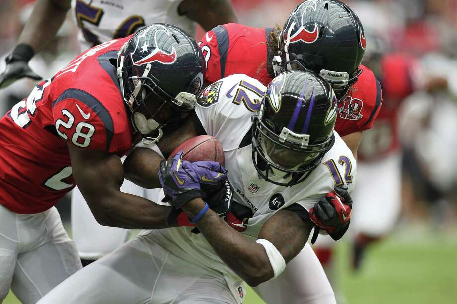 Baltimore Ravens wide receiver Jacoby Jones (12) is tackled by Houston Texans linebacker Bryan Braman (50) and running back Justin Forsett (28) during the second quarter of an NFL football game, Sunday, Oct. 21, 2012, at Reliant Stadium in Houston. Photo: Nick De La Torre, Houston Chronicle / © 2012  Houston Chronicle