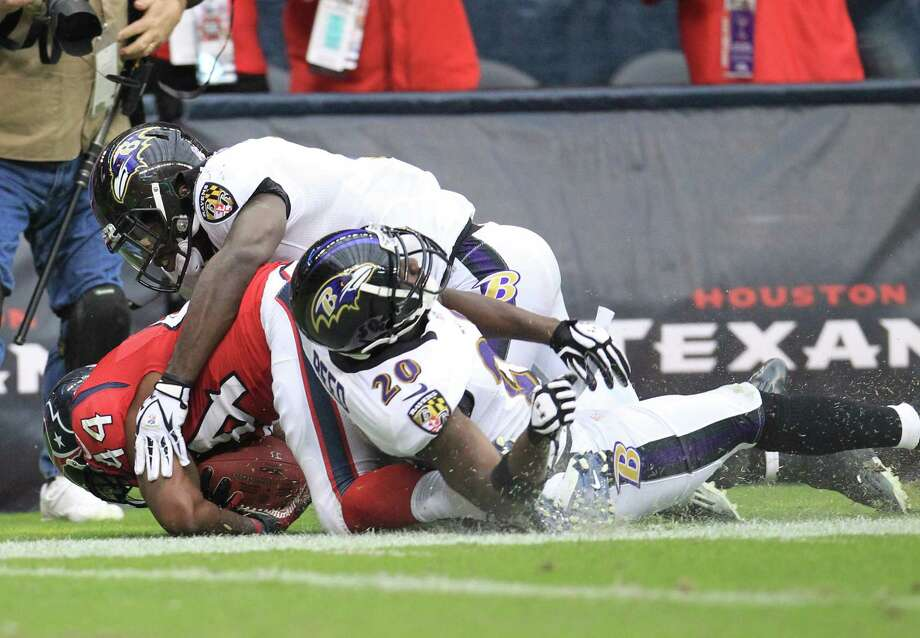 Houston Texans running back Arian Foster (23) is tackled near the end zone by Baltimore Ravens linebacker Dannell Ellerbe (59) and Baltimore Ravens strong safety Bernard Pollard (31) during the fourth quarter of an NFL football game at Reliant Stadium, Sunday, Oct. 21, 2012, in Houston. Texans won 43-13. Photo: Karen Warren, Houston Chronicle / © 2012  Houston Chronicle