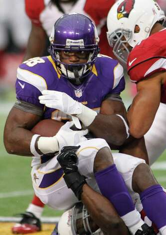 Minnesota Vikings running back Adrian Peterson (28) is tackled by Arizona Cardinals strong safety Adrian Wilson (24) and linebacker Paris Lenon (right) in the first half in Minneapolis, Sunday, Oct. 21, 2012. Photo: Andy King, Associated Press / FR51399 AP