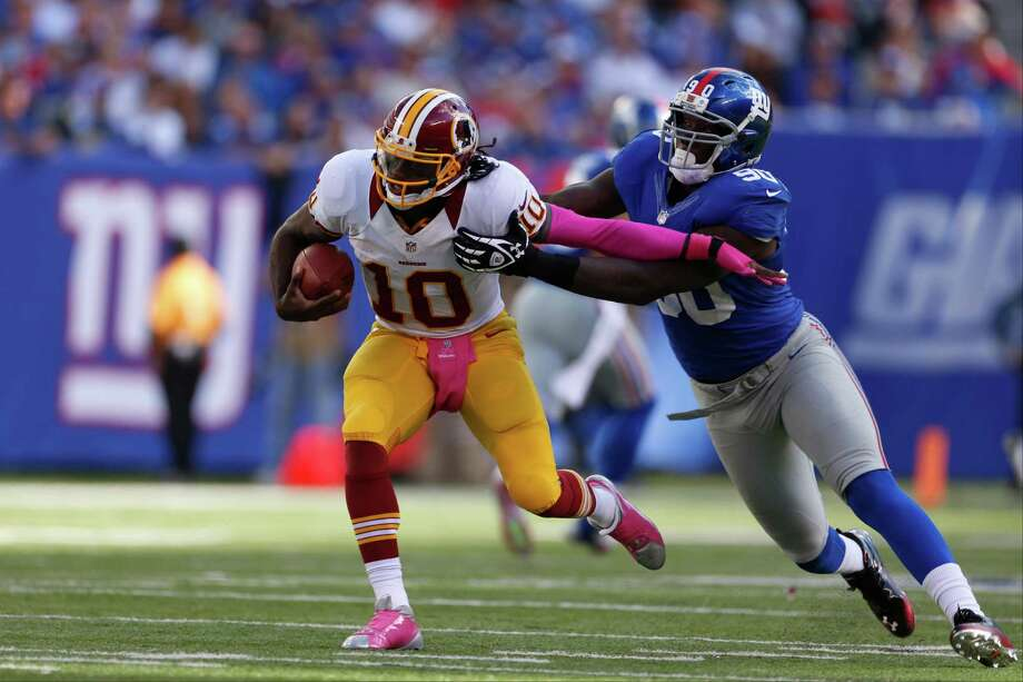New York Giants defensive end Jason Pierre-Paul (90) tries to sack Washington Redskins quarterback Robert Griffin III (10) during the second half of an NFL football game Sunday, Oct. 21, 2012 in East Rutherford, N.J. (AP Photo/Julio Cortez) Photo: Julio Cortez, Associated Press / AP