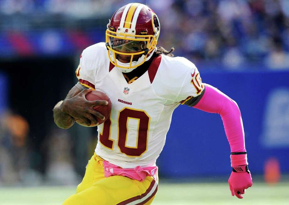 Washington Redskins quarterback Robert Griffin III carries the ball against the New York Giants during an NFL football game, Sunday, Oct. 21, 2012, in East Rutherford, N.J. The Giants won 27-23. (AP Photo/The Record of Bergen County, Tyson Trish) MAGS OUT; TV OUT; NO ARCHIVING; MANDATORY CREDIT Photo: Tyson Trish, Associated Press / The Record of Bergen County