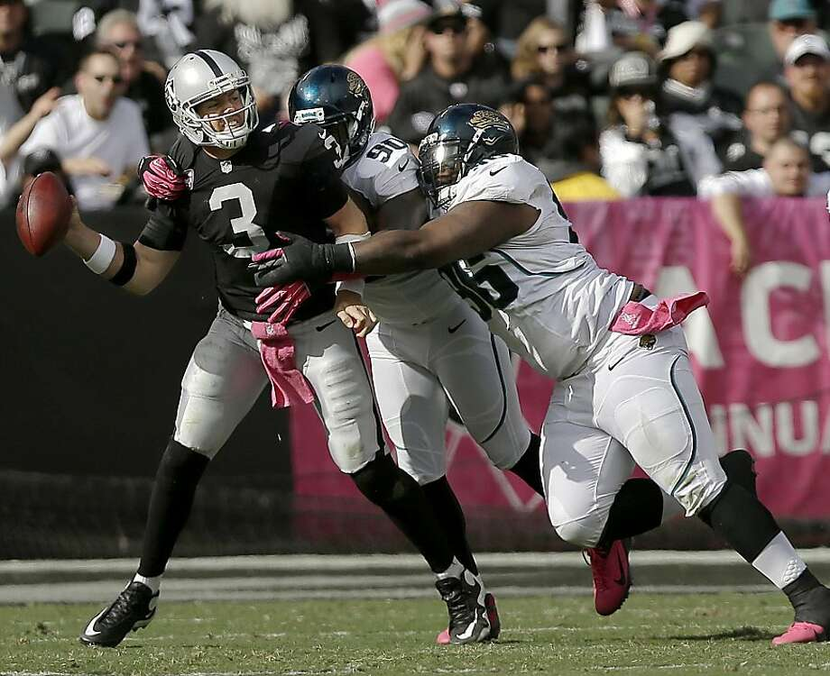 Carson Palmer stands up to pass rushers Andre Branch (center) and Terrance Knighton during the Raiders' second-half resurgence. Photo: Marcio Jose Sanchez, Associated Press