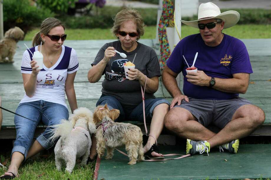 Brandi Hignite, left, of Tomball and her parents Janet Talley and Wayne Talley, right, of Tomball take a break with their dogs, Carlee and Maggie, during Pet Fest in Old Town Spring Sunday, Oct. 21, 2012, in Spring. Photo: Melissa Phillip, Houston Chronicle / © 2012 Houston Chronicle