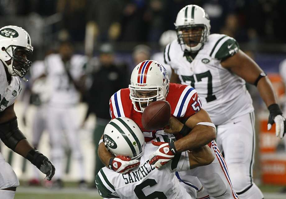 Patriots defensive end Rob Ninkovich separates Jets quarterback Mark Sanchez from the ball, clinching the win for New England in overtime. Photo: Stephan Savoia, Associated Press