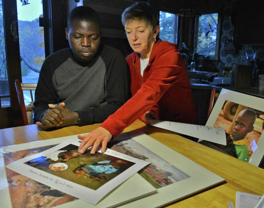 Ugandan Ronnie Sseruyange, left, and Diane Reiner look over some of Diane's photographs of homeless youth on the streets of Kampala, Uganda  in the kitchen of Diane's Colonie home Friday Oct. 19, 2012. Reiner met Sseruyange after he was living as a homeless youth on the streets in Uganda. Now, Reiner has started a program, Jajja's Kids, to help the street kids of Kampala.  (John Carl D'Annibale / Times Union) Photo: John Carl D'Annibale / 00019759A