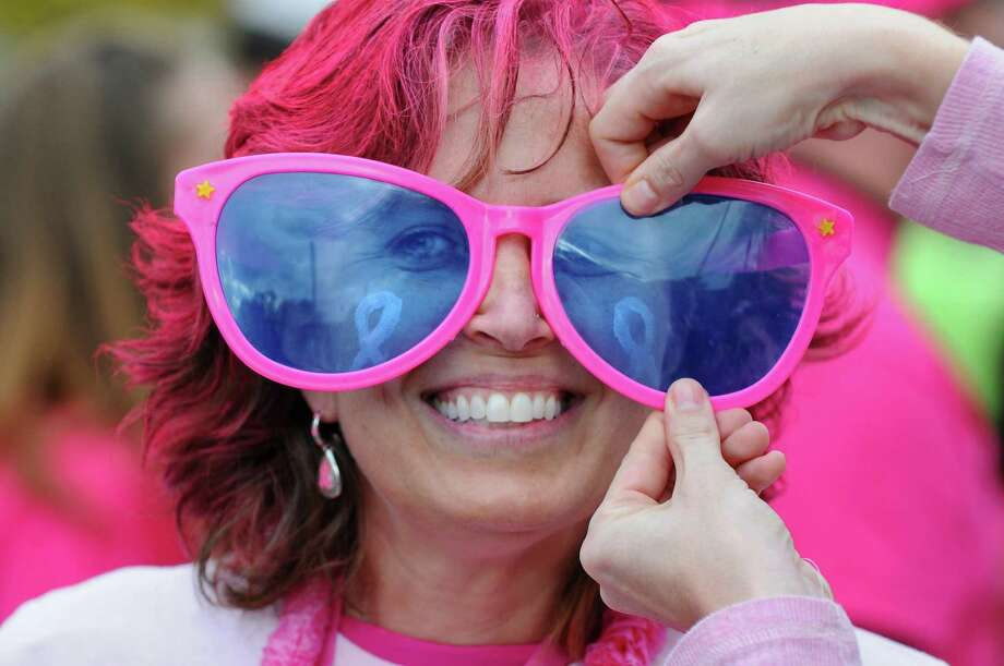 A one year survivor of breast cancer has her sunglasses adjusted as she walks in Washington Park during the Making Strides Against Breast Cancer walk on Sunday Oct. 21, 2012 in Albany, NY.  Over 15, 000 people walked through the park, raising over $1 million, according to Rebecca Colino of the American Cancer Society. (Philip Kamrass /  Times Union) Photo: Philip Kamrass / 00019712A