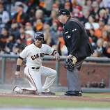 Giants' second baseman Marco Scutaro scores in the first inning off a Buster Posey sacrifice during game 2 of the NLCS at AT&T Park on Monday, Oct. 15, 2012 in San Francisco, Calif.