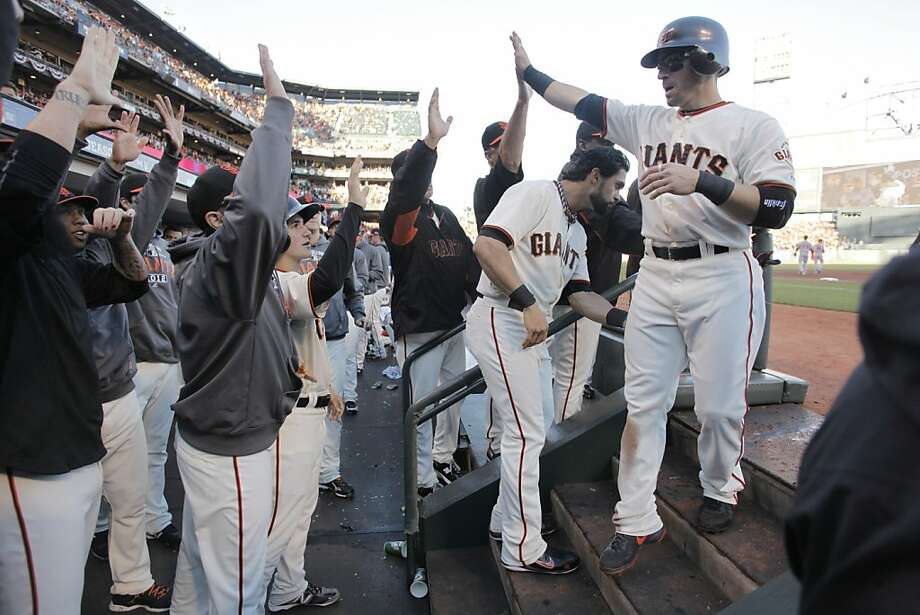 Marco Scutaro (right) is welcomed after scoring Sunday's first run. He finished with two hits, two runs, two RBIs and a walk. Photo: Michael Macor, The Chronicle