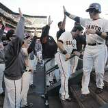 Giants' second baseman Marco Scutaro is greeted in the dugout after scoring in the 1st inning during game 6 of the NLCS at AT&T Park on Sunday, Oct. 21, 2012 in San Francisco, Calif.